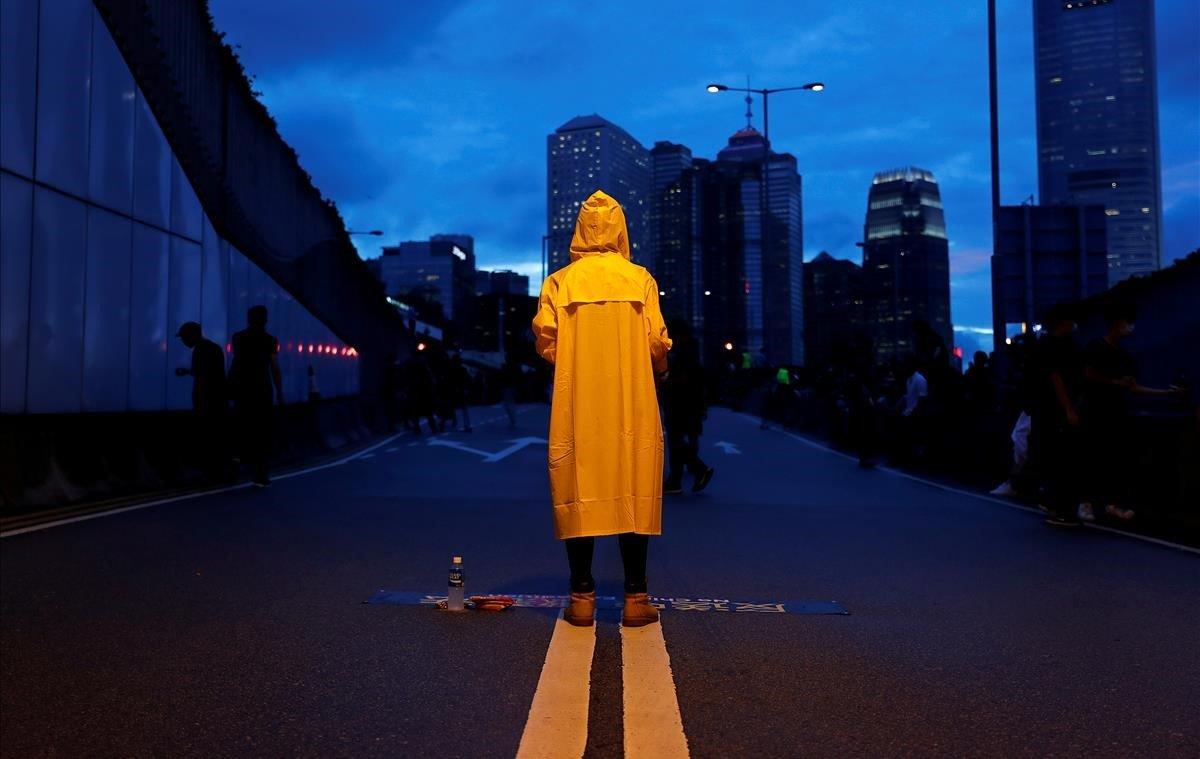 Un manifestante usa un impermeable amarillo para rendir homenaje a un hombre que murió tras caerse de un andamio en el complejo Pacific Place mientras protestaba contra el proyecto de ley de extradición, durante una manifestación que exigía a los líderes de Hong Kong que renuncien y retiren el proyecto de ley de extradición en Hong Kong.