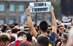 Un estudiante en Plaza Catalunya alza una pancarta con el mensaje: Todo el mundo al aeropuerto.