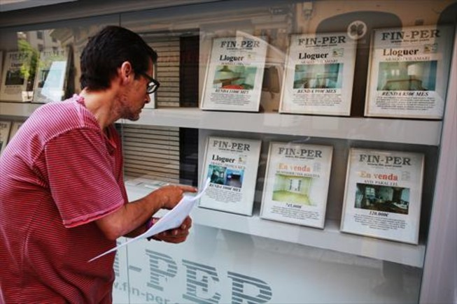 Un hombre mirando ofertas de pisos de alquiler en los expositores de una inmobiliaria del barrio del Poble Sec de Barcelona.