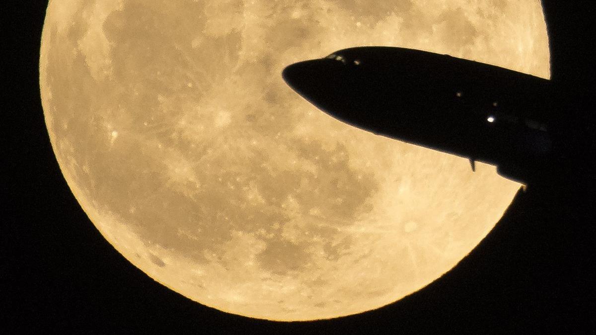 Un avión que despega del Aeropuerto Nacional Ronald Reagan se ve pasar frente a la luna a medida que se eleva en Washington.