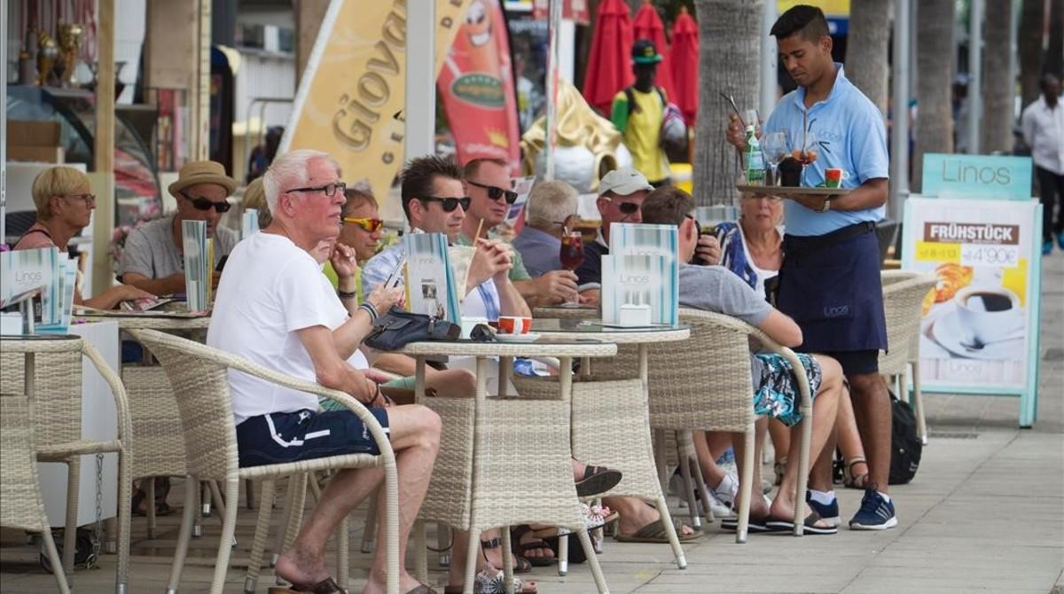 Un camarero atiende a unos turistas en una terraza de Palma de Mallorca.