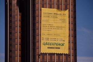La pancarta de casi 300 metros cuadrados que ha desplegado Greenpeace en la fachada de las torres de Colón.