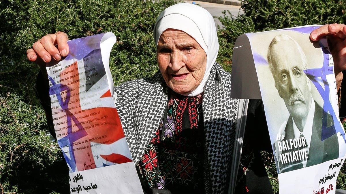Una mujer palestina sostiene una fotografia partida en dos de Arthur Balfour en el exterior de la embajada británica en Beirut.