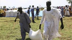Dos hombres cargan un saco de comida facilitada por el PAM durante una visita de una delegación de la UE, en Azaza, este miércoles.