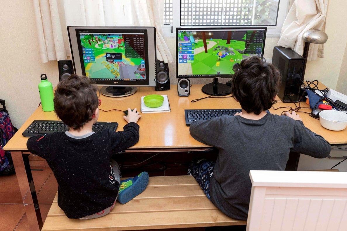 Dos niños juegan en sus ordenadores durante el confinamiento, en Murcia, el 28 de marzo.