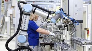 Un brazo robotizado, junto a una trabajadora, en la fábrica de Volkswagen en Salzgitter (Alemania).