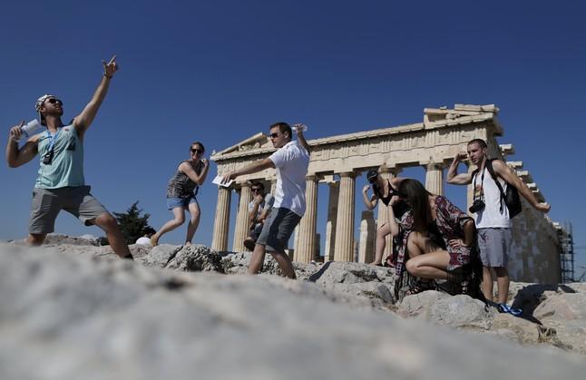 Un grupo de turistas se fotografían frente al Partenón.