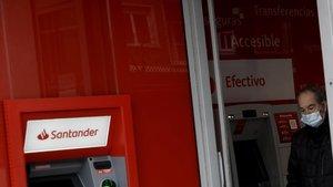 Un hombre con mascarilla saca dinero de un cajero del Banco Santander en Madrid, el pasado 21de abril.