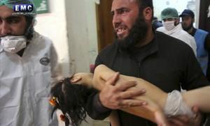 Un hombre lleva en brazos a un niño herido por gas tóxico en Idleb.