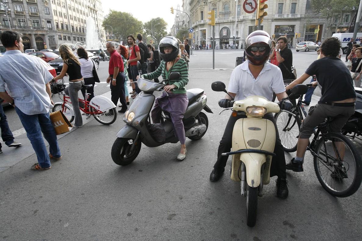 Bicis, peatones, motos y coches, en una calle de Barcelona.