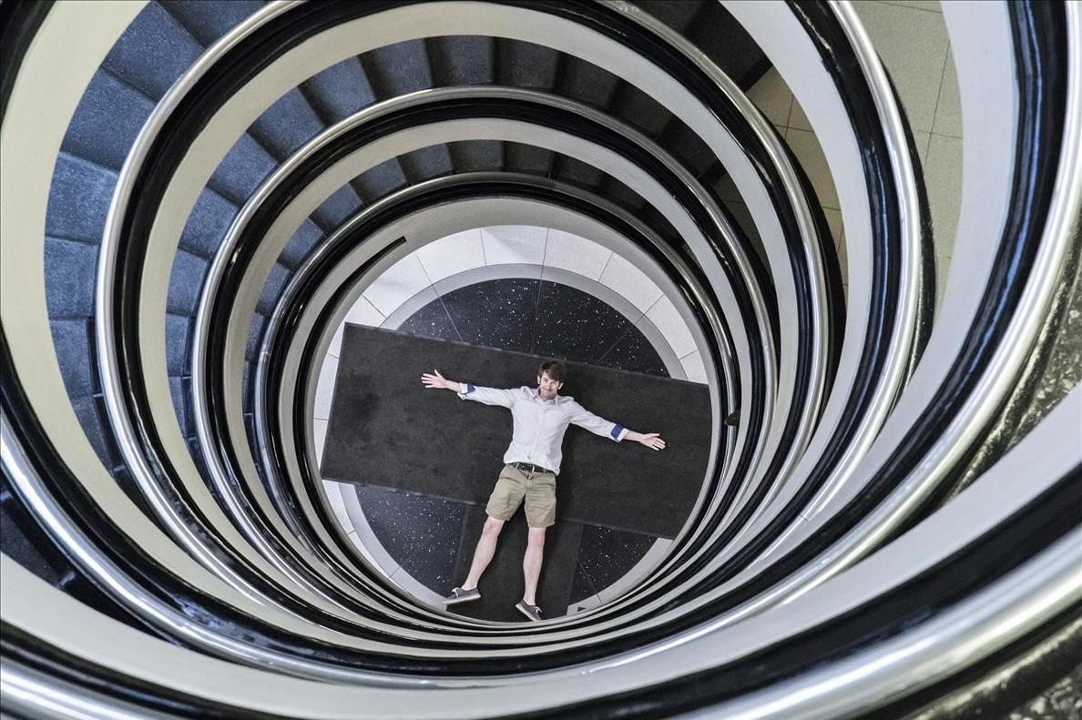 El fotógrafo Gauvin Lapetoule, en la entrada de la clínica Barraquer, bajo su hipnótica escalera de caracol de siete pisos.
