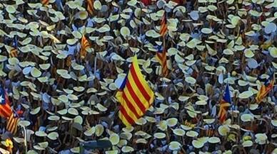 Los manifestantes levantan los puntos de cartulina repartidos por la ANC, en la marcha de Barcelona, a su paso por el paseo de Sant Joan.