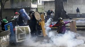 Manifestantes chocan con las fuerzas de seguridad chavistas durante una marcha en Caracas, el 1 de mayo.