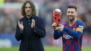 Messi recibe de manos de Puyol el trofeo que le acredita como el mejor jugador de la Liga en diciembre pasado.