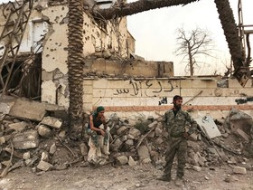 Militares del Ejército sirio enfrente de un edificio destrozado en un distrito de Deir Ezzor. Imagen del5 de noviembre de 2015.