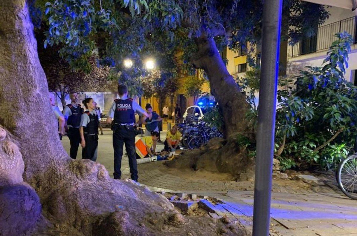 Mossos y personal sanitarioatienden al joven herido anoche en Poblenou.