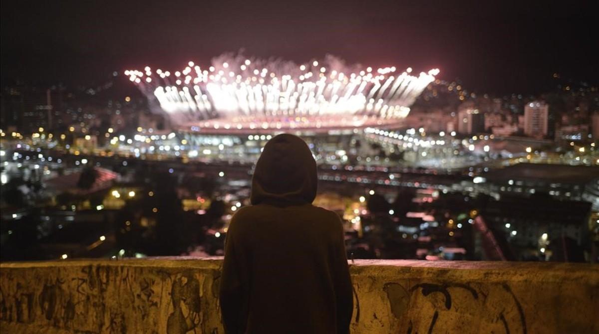 Un niño observa desde el Morro da Mangueiralos fuegos artificiales de Maracaná durante la ceremonia de clausura de los Juegos.