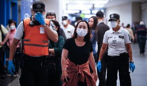 Policías argentinos separan a turistas europeos a su llegada al aeropuerto Jorge Newbery de Buenos Aires, en prevención por la pandemia de coronavirus.