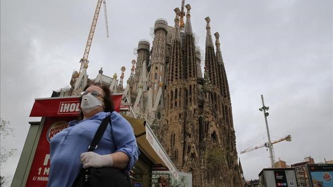 Segundo día del estado de alarma por el coronavirus. En la foto, una mujer se protege con mascarilla frente a la Sagrada Família.