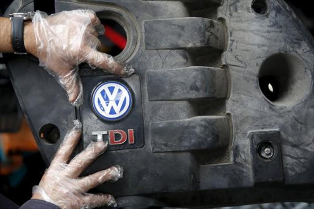 Un operario coloca la tapa de un motor diésel VW .