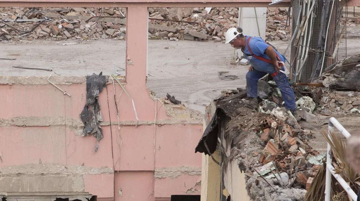 Un trabajador con arnés de protección pero sin anclar, en una obra de Barcelona.