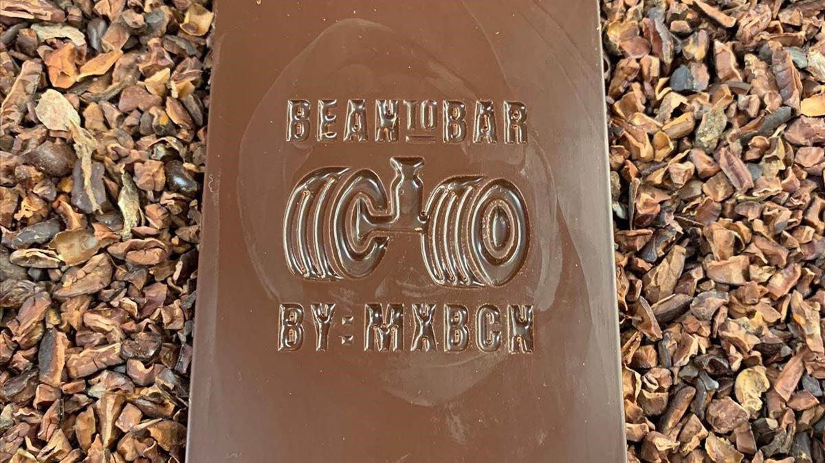 Una barrita elaborada artesanalmente en Bean to bar, en el Museu de la Xocolata, reposa sobre habas de cacao.