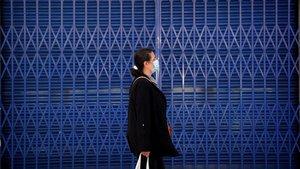 Una mujer con mascarilla pasa junto a un comercio temporalmente cerrado por la crisis del covid-19