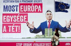 Una mujer pasajunto a un cartel en el que se critica al primer ministro de Hungría, Viktor Orban, por amenazar la unidad de Europa, en los alrededores del Parlamento Europeo, en Bruselas.
