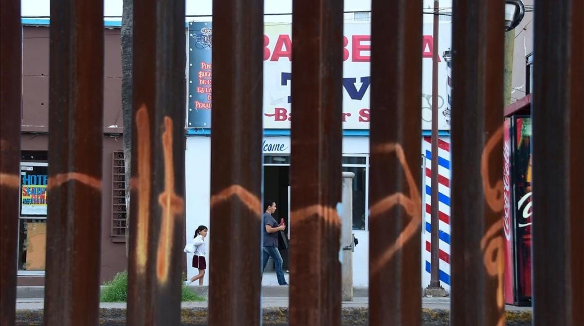 Una mujer y una niña pasan por delante de una barbería en Nogales, en el estado de Sonora (México), vistos a través de la valla fronteriza desde Nogales (Arizona), el 12 de octubre del 2016.