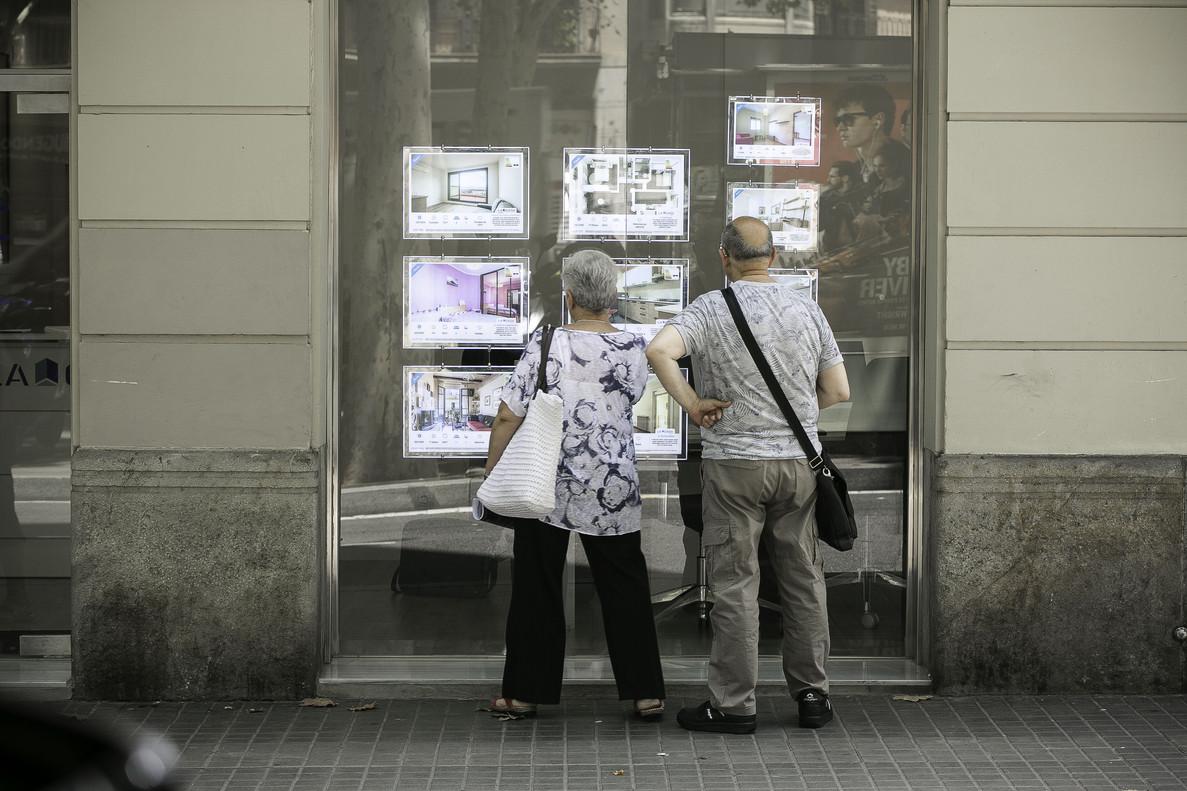 Una pareja consultaprecios de pisos en una agencia inmobiliaria de Barcelona.