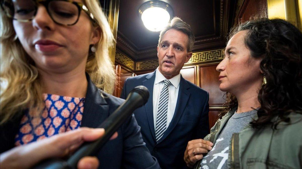 Una presunta víctima de violación, a la derecha, increpa al senador Jeff Flake.