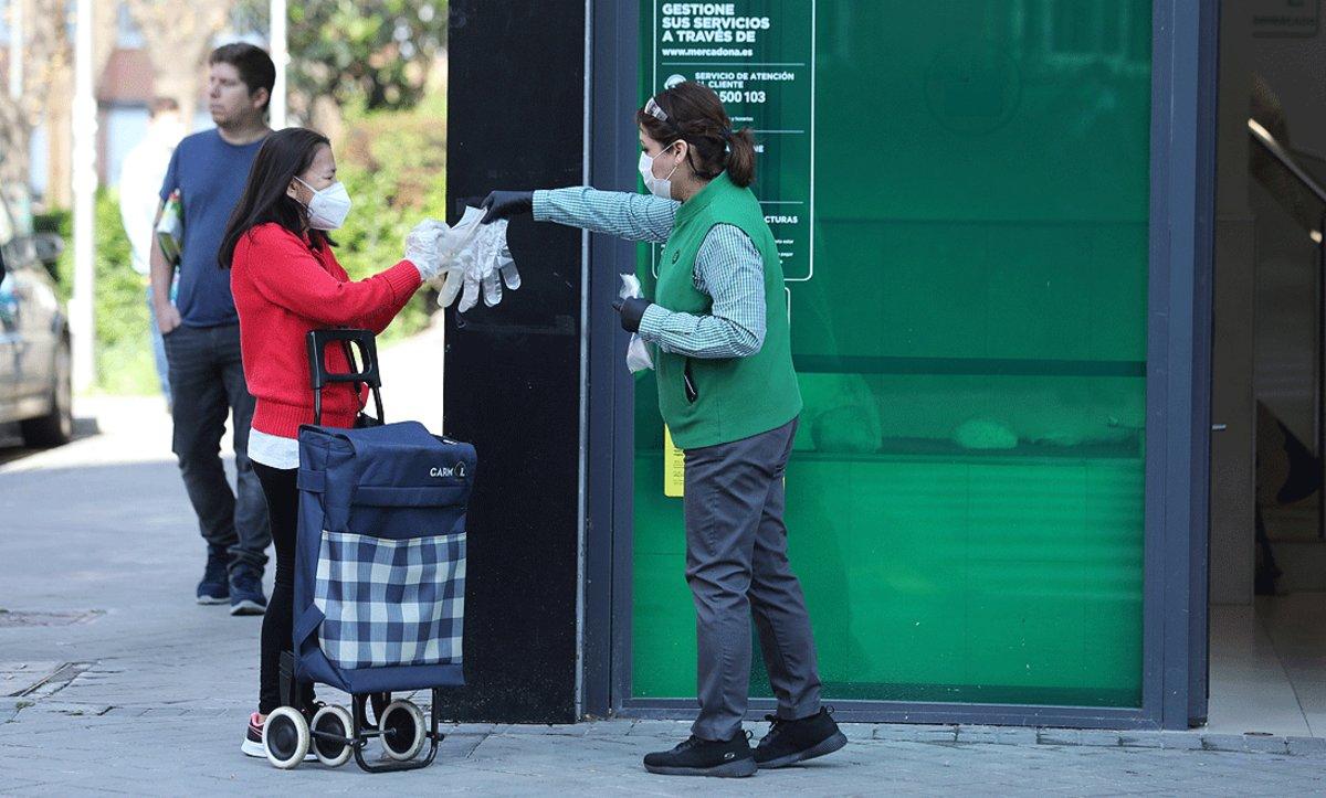 Una trabajadora de un supermercado entrega un par de guantes a una clienta, en Madrid, el pasado 8 de abril.