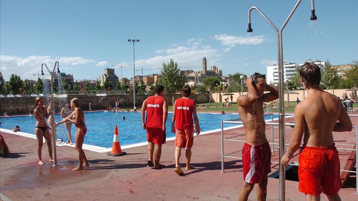 Unos jóvenes se refrescan en una piscina pública.