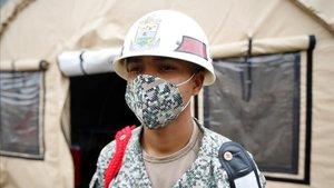 Un soldado colombiano con una mascarilla monta guardia en un estacionamientodonde se han levantado tiendas medicalizadas juntoa un hospital militar en Bogotá.