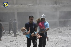 Voluntarios de la Defensa Civil con niños, tras un bombardeo en Daraa.