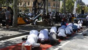 Taxistas paquistanísrezan en el paseo de Gràcia durante la huelga del sector.
