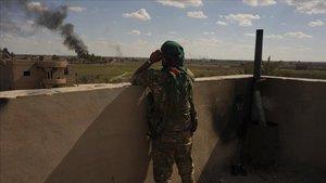 Un miembro del Ejército Libre Sirio observa el humo del ataque de fuerzas estadounidenses al último bastión del territorio en manos de Estado Islámico.