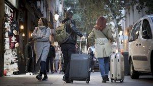 Turistas con maletas por la calle de Argenteria.