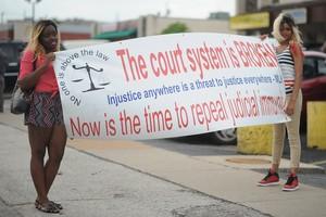 Dos jóvenes protestan en Ferguson con una pancarta contra el sistema judicial estadounidense.