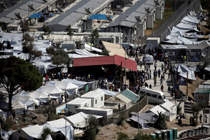 FILE PHOTO - Refugees and migrants line up for food distribution at the Moria migrant camp on the island of Lesbos