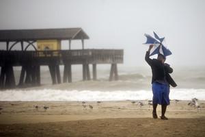 Un hombre intenta sostener su paraguas en una playa estaounidense.