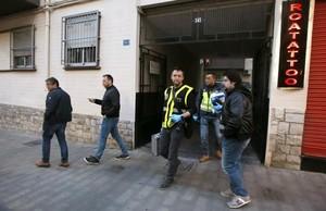 Agentes de la policía científica salen del edificio donde se ha producido el suceso.