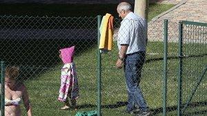 Un abuelo cuida de su nieta en la piscina de la urbanización en la que vive, a las afueras de Madrid.