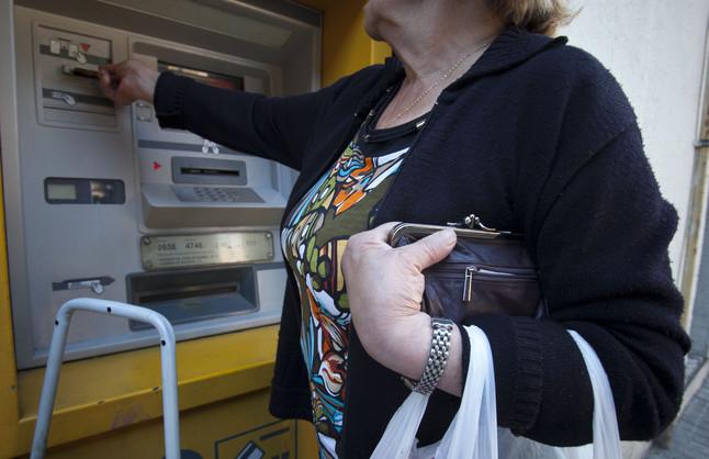 Una mujer mayor sujeta su monedero mientras saca dinero de un cajero en Barcelona.