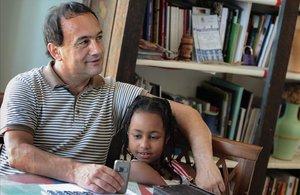 El alcalde de Lucano, Domenico Lucano, con una niña originaria de Etiopía.