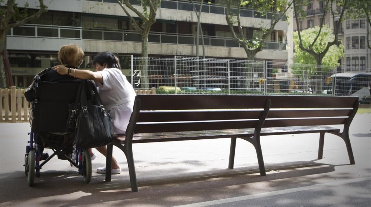 Un anciano con su cuidador en el paseo de Sant Joan en Barcelona.