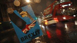 Un autobús pasa junto a un cartelanti-brexit situado cerca del Parlamento en Londres.