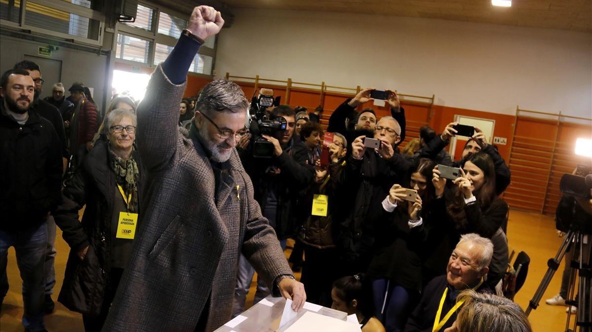 El candidato de la CUP, Carles Riera, ejerce el voto con el puño alzado.