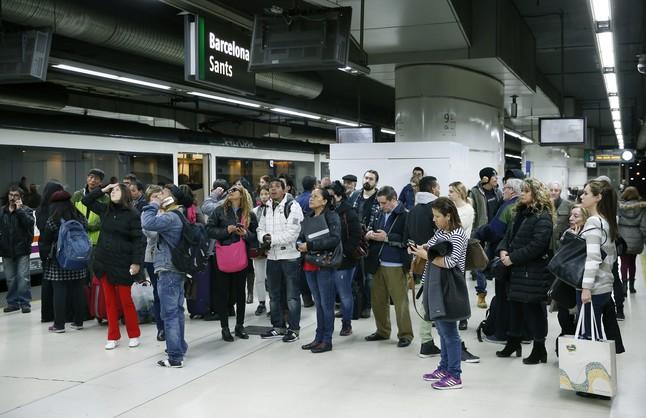 Un grupo de viajeros observa los paneles informativos en la estación de Sants de Barcelona.