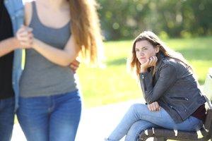 Una chica sentada en el parque siente envidia al ver a una pareja.